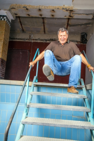 waterless: man jumping down the stairs of an old waterless pool Stock Photo