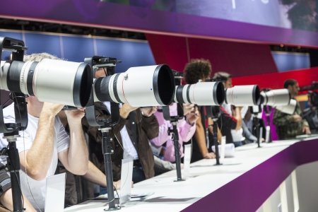 PHOTOKINA, COLOGNE - SEPTEMBER 21: Photokina - World of Imaging, Top Event for the Trade and User, September 21, 2012 in Cologne, Germany. Visitors test huge tele lenses. Stock Photo - 15337076