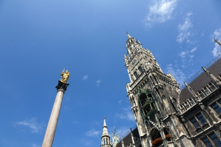 MUNICH, GERMANY - JULY 9: Clock of the old City Hall at Marienplatz with Mary statue on July  9,2012 in Munich, Germany.  The facade of the townhall with the golden Mary are a famous attraction for tourists.