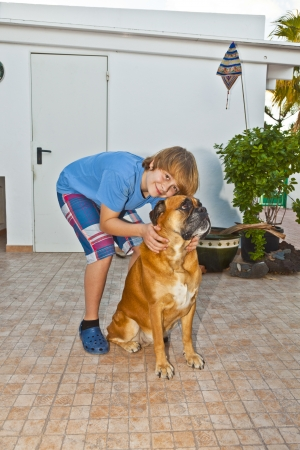 boy playing with his friedn, a boxer dog photo