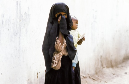 HADHRAMAUT, YEMEN - MAY, 15: arabic unknown mother carries her baby in a  wraparound garment on May 15,1993 in Hadhramaut, Yemen. in 2008 still 62 percent of women in rural areas are  illiteracy.