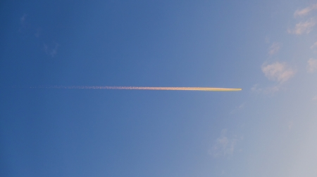 beautiful blue sky with condensation trail of an aircraft photo