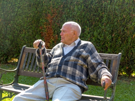 old man enjoys sitting on a bench in his garden photo