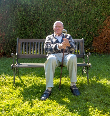 old man enjoys sitting on a bench in his garden