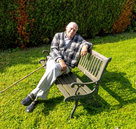 old man enjoys sitting on a bench in his garden Reklamní fotografie