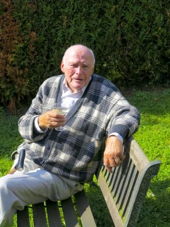 granddad: old man enjoys sitting on a bench in his garden