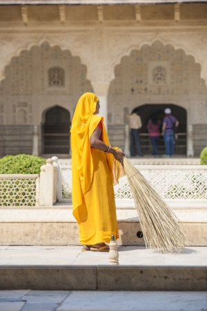 AMER, INDIA - 19 NOVEMBER: woman of fourt class in brightly colored clothing cleans the Amber palace in Amer on November 19,2012 in Amber,India. They earn 300 IRP for two hours paid by the government.
