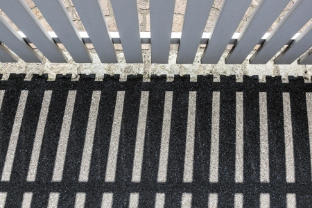 repetitious: shadow of wooden fence at the street Stock Photo