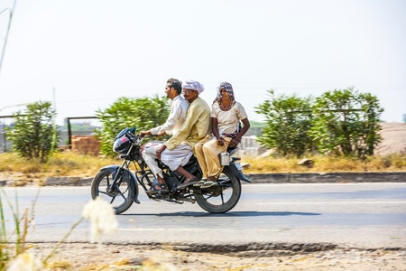 RAJASTHAN - INDIA - OCTOBER 18: Mother, father and small child riding on scooter through busy highway street on October 28, 2012 in Rajasthan, India. Up to six family members manage to ride these two wheelers.