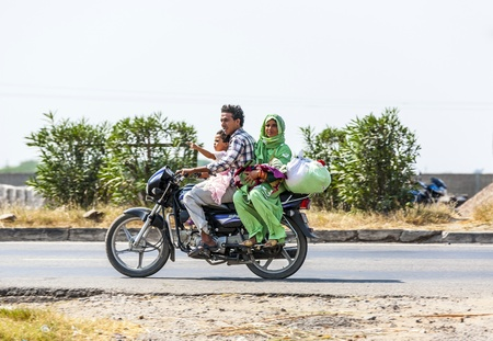 RAJASTHAN - INDIA - OCTOBER 17: Mother, father baby and small child ride scooter at the highway on October 17, 2012 in Rajasthan, India. Up to six family members manage to ride these two wheelers.