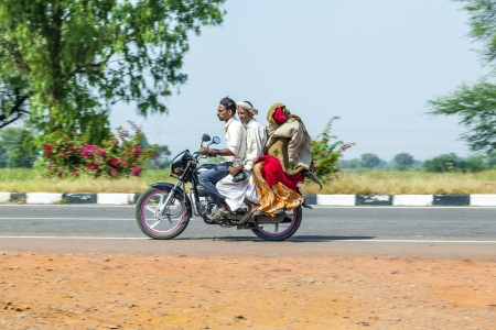 RAJASTHAN - INDIA - OCTOBER 18: Mother, father and small child riding scooter through busy highway street on October 18, 2012 in Rajasthan, India. Up to six family members manage to ride these two wheelers.