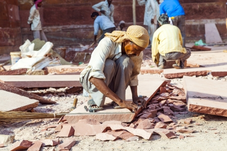 mentioned: AGRA, INDIA - OCTOBER 17: worker prepares sandstones for renovation of the Red Fort on October 17,2012 in Agra, India. The fort was mentioned for the first time in 1080 AD when a Ghaznavide force captured it.