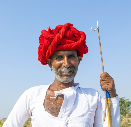 PUSHKAR, INDIA - OCTOBER 22: A Rajasthani tribal man wearing traditional colorful turban and loves to pose  at the annual Pushkar Cattle Fair on October 22, 2012 in Pushkar, Rajasthan, India.