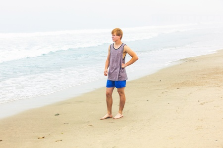 cute young teenage boy has fun at the beach photo