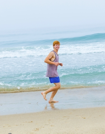 cute young teenage boy joging at the empty beach in the morning photo