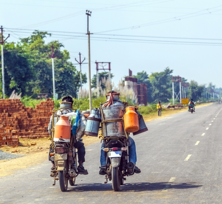milkman: RAJASTHAN, INDIA - OCTOBER 18: men riding motorbike with cans of milk on October 18, 2012 in Rajasthan, India. These motorized milkman reach also the small villages.