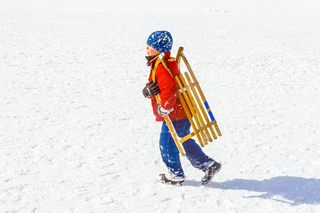 child carries his sledge up the hill in wintertime photo