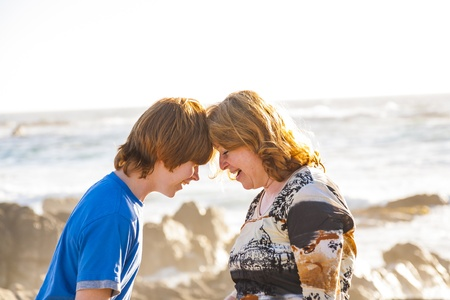 mother and son enjoy the afternoon sun at the beach photo