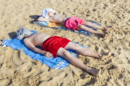 young cute boys sleep at the beach photo