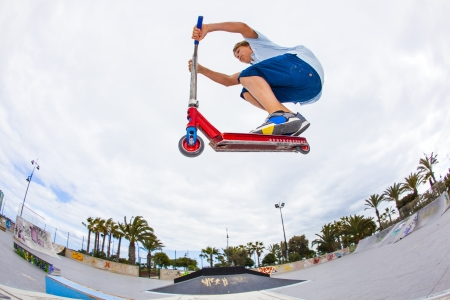 boy has fun jumping with his scooter at the skate park