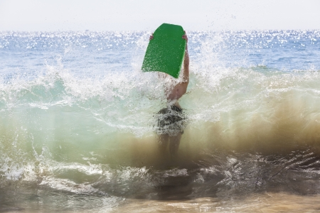 boy has fun surfing in the waves photo