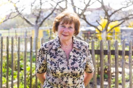 happy elderly woman is standing proud in her garden and smiles Stock Photo - 16864670