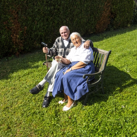 elderly couple sitting in their garden and enjoy life photo