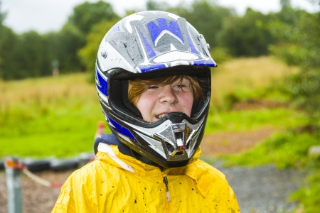happy boy with helmet at the kart trail in rain with dirty face and clothing photo