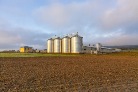 Silo in beautiful landscape with dramatical light placed in plouged acres photo
