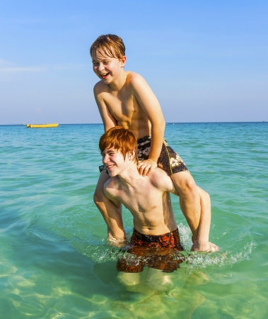 brothers are enjoying the clear warm water at the beautiful beach and playing pickaback photo