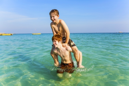 brothers are enjoying the clear warm water at the beautiful beach and playing pickaback Stock Photo - 16952393
