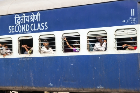 JAIPUR, INDIA - OCTOBER 23  Unidentified passengers hanging at the window of a moving Indian Railway train on October 23,2012 in Jaipur, India  Indian Railways carries  about 7,500 million passengers annually
