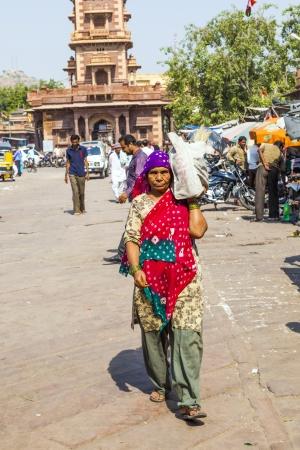 maharaja: JODHPUR, INDIA - OCTOBER 23: woman carrys goods on the shoulder at the Sadar market at the clocktower on October 23,2012 in Jodhpur, India. The imposing Clock Tower was built by Maharaja Sardar Singh (1880-1911). Editorial
