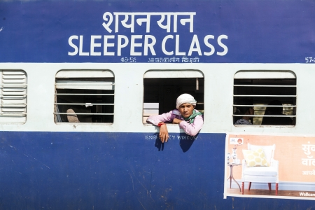 JAIPUR, INDIA - OCTOBER 23: Unidentified passengers hanging at the window of a moving Indian Railway train on October 23,2012 in Jaipur, India. Indian Railways carries  about 7,500 million passengers annually.