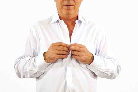 buttoning: man buttoning his white office shirt in the morning