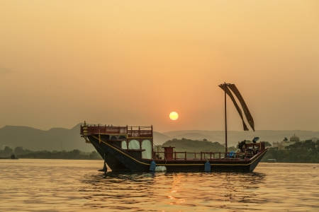 sun drenched: Sunset with Boat  in Udaipur,india Stock Photo