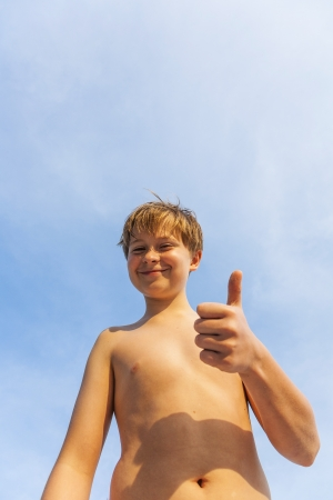 happy smiling young boy is posing at the beach under blue sky photo