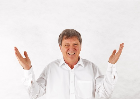Portrait of a happy senior man standing gesturing against white background Stock Photo - 17054239