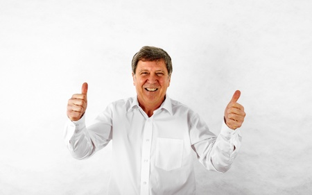 Portrait of a happy senior man standing gesturing against white background Stock Photo - 17054258
