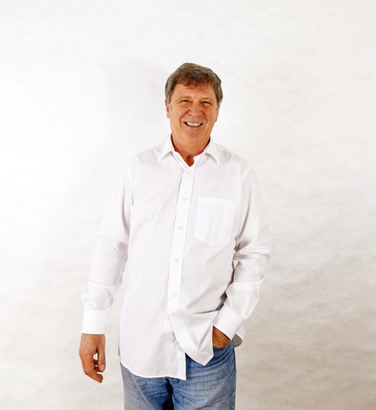 Portrait of a happy senior man standing gesturing against white background photo