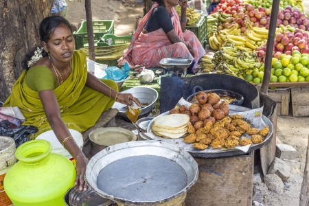 mamallapuram: MAMALLAPURAM, INDIA - AUGUST 25: Unidentified Indian women in brightly colored saris sells bread and fresh boiled cakes by the side of the road. August 25, 2012 in Mamallapuram, India.