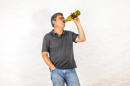mature man drinks alcohol out of a bottle Stock Photo - 17076823