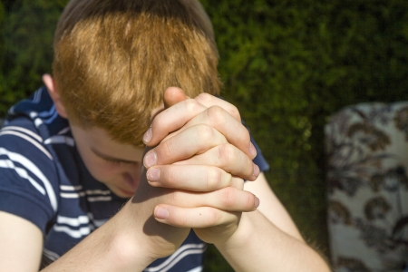 young red haired boy has his hands folded as praying photo