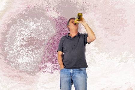 delirium: mature man drinks alcohol out of a bottle