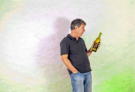 mature man drinks alcohol out of a bottle photo