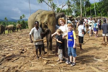 PINNAWELLA, SRI LANKA AUGUST 8: children hug with elephants in the jungle camp on Aug 8, 2005 in Pinnawella, Sri Lanka. The  Elephant Orphanage was opened in 1975. Stock Photo - 17069751
