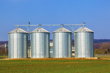 four silver silos in field under bright sky