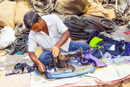 maschine: ORISSA, INDIA - NOV 10 - Indian men tailors run their sewing machines in the shade at the weekly market on Nov 10, 2009 in Orissa, India. Editorial