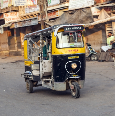 auto rickshaw: JODHPUR, INDIA - OCT 23: Auto rickshaw taxi driver on October 23,2012 in Jodhpur, India. These iconic taxis have recently been fitted with CNG powered engines in an effort to reduce pollution. Editorial