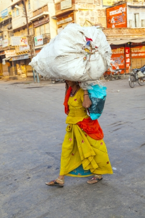 JODHPUR,INDIA - OCT 23: Indian woman carries heavy load on her head on Oct 23, 2012 in Jodhpur, India. Indian women work more than men but their work is hardly recognized as they do unskilled work.